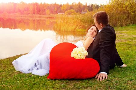 newlyweds sitting on the grass on nature photo