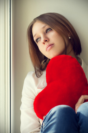 love hurts: The girl is sad, sadness due the guy, keep heart sit near the window
