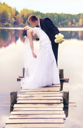 young couple kissing on the bridge on nature photo