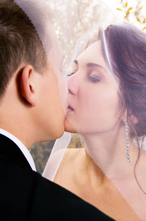 newlyweds kiss on nature photo