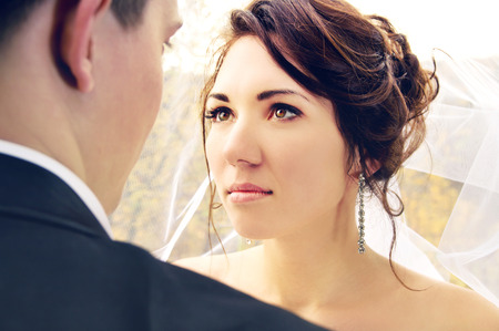 newlyweds look at each other on nature photo