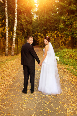 young couple looking back, holding for hands on nature photo