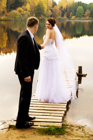 young couple standing on the bridge on nature photo