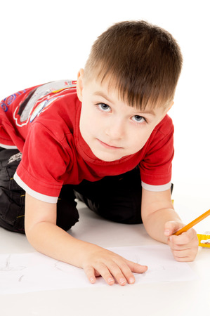 a little boy draws on the paper isolated on white background photo