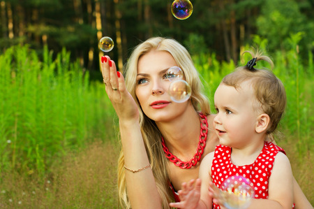 Happy mother and child with soap bubbles on nature background photo