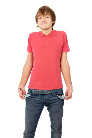 turned out: the handsome young man turned his pockets out and shows that he has nothing isolated on white background