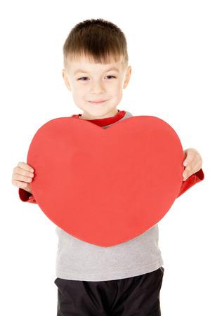 ein kleines Kind steht und hält das Herz auf weißem Hintergrund Standard-Bild