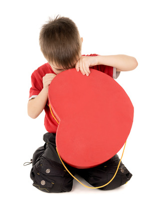 snooping: a small child looks cardboard box, in the form of heart isolated on white background