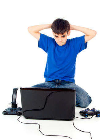 dependent: boy with a laptop and joystick thinks Stock Photo