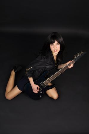 girl playing guitar: Beautiful girl playing guitar on a black background