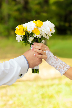 Bouquet keep the bride and groom on the background of nature
