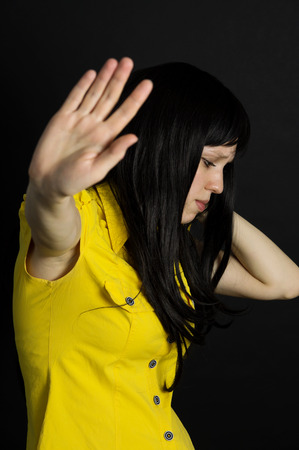 Violence, suffering girl showing stop hand on a black background