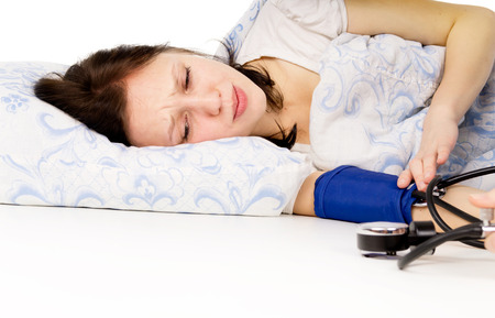 diseased: the diseased girl lying on the bed, and measure the pressure isolated on white background