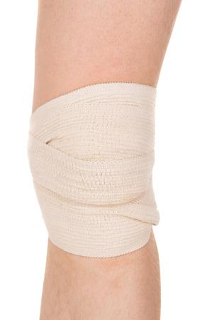 luxacion: vendar la rodilla con una venda el�stica aislados sobre fondo blanco Foto de archivo