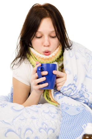 diseased: the diseased girl lying in bed, drinking tea isolated on white background