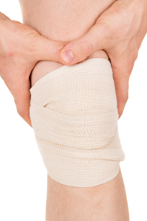 convulsions: bandaging the knee with an elastic bandage isolated on white background Stock Photo