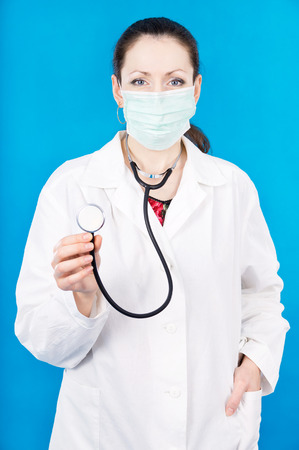 young doctor in a mask holds stethoscope on a blue background