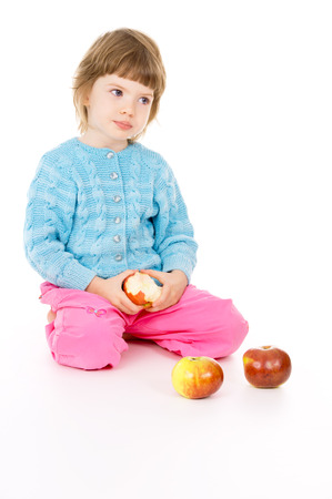 a beautiful little, girl eats apples isolated on white background
