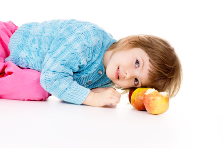 a beautiful little girl lying next to apples isolated on white background