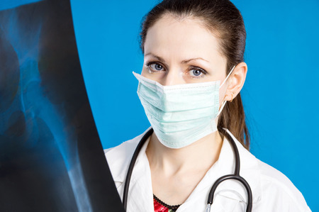 doctor in a mask holds x-ray on a blue background