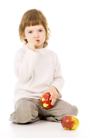 a beautiful little girl eat apples isolated on white background