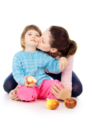 mother and daughter eat apples isolated on white background