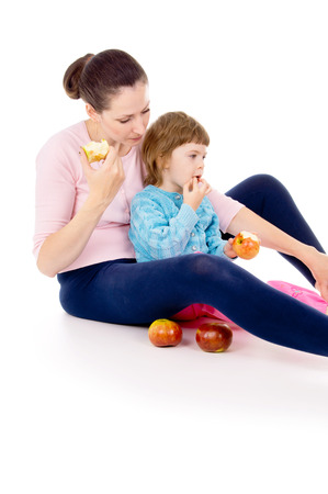 mother with a child sit and eat apples isolated on white background