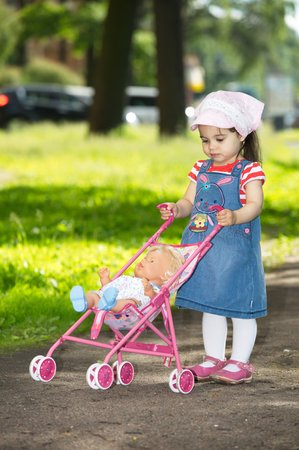Little girl is walking with her baby doll at park  photo