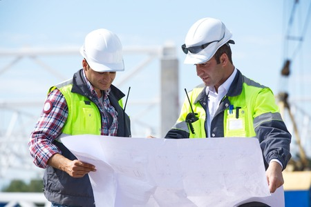 Two engineers at construction site are inspecting works according to design drawings  Stock Photo