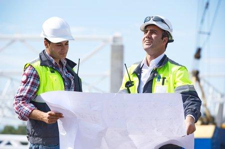 Two engineers at construction site are inspecting works according to design drawings  photo