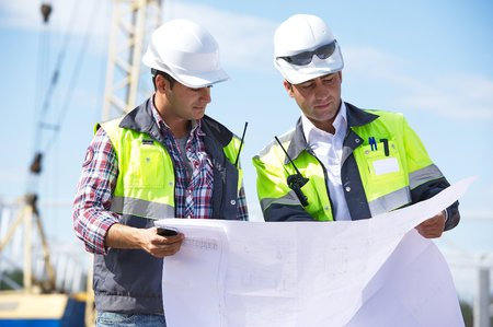 business project: Two engineers at construction site are inspecting works according to design drawings  Stock Photo