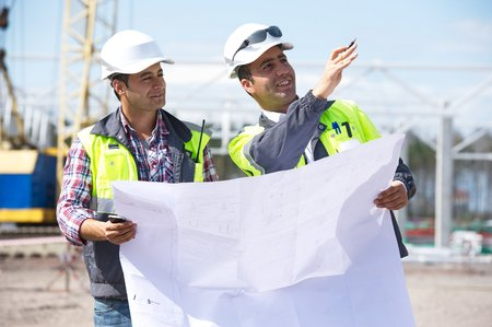 engineering drawing: Two engineers at construction site are inspecting works according to design drawings  Stock Photo
