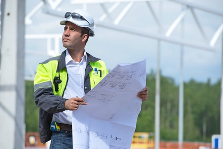 Engineer at construction site is inspecting works according to design drawings  Stock Photo