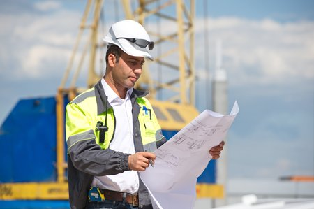 Engineer at construction site is inspecting works according to design drawings  Standard-Bild