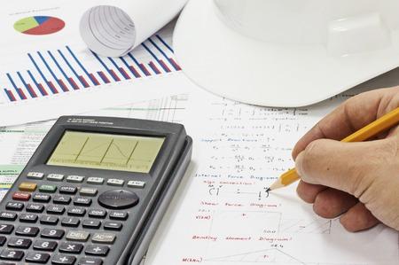 ingeniero civil: Civil Design Engineer est� haciendo c�lculos de an�lisis estructurales utilizando una calculadora cient�fica.