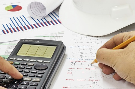 structural engineers: Civil Design Engineer is making structural analysis calculations using a scientific calculator. Stock Photo