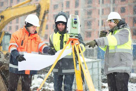 Los ingenieros civiles en el sitio de construcción están inspeccionando las obras en curso de acuerdo con los planos de diseño en las difíciles condiciones invernales