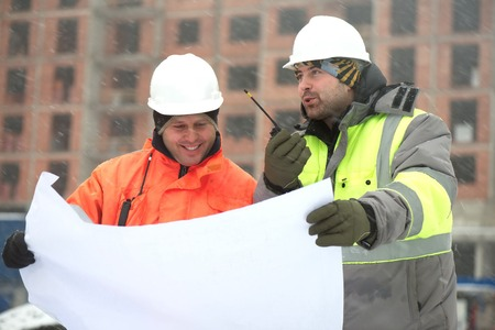 according: Civil engineers at construction site are inspecting ongoing works according to design drawings in difficult winter conditions