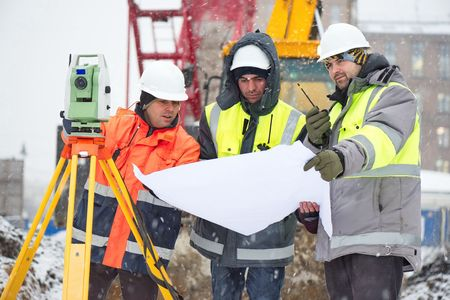 Civil engineers at construction site are inspecting ongoing works according to design drawings in difficult winter conditions