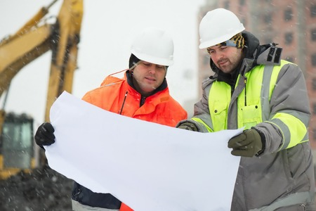 civil construction: Civil engineers at construction site are inspecting ongoing works according to design drawings in difficult winter conditions
