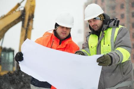 ingeniero civil: Los ingenieros civiles en el sitio de construcci�n est�n inspeccionando las obras en curso de acuerdo con los planos de dise�o en las dif�ciles condiciones invernales