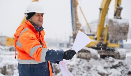 construction project: Civil engineer at construction site is inspecting ongoing works according to design drawings in difficult winter conditions Stock Photo
