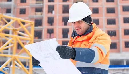 Civil engineer at construction site is inspecting ongoing works according to design drawings in difficult winter conditions Standard-Bild