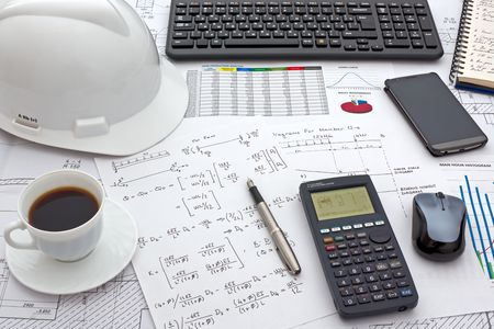 Desk of Civil Design Engineer who has just made structural analysis calculations using a scientific calculator.