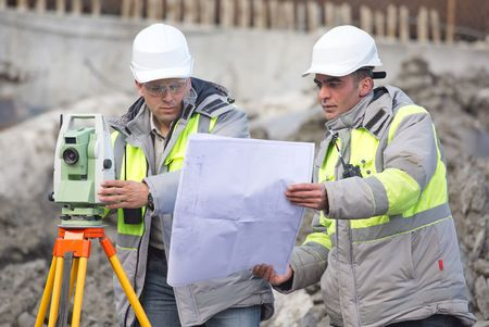 teodolito: Ingeniero Civil y Topógrafo en el sitio de construcción están inspeccionando la producción en curso de acuerdo a los planos de diseño.