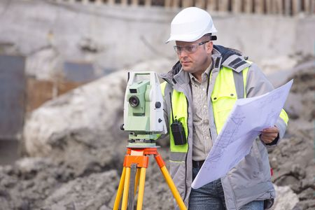 Surveyor at at construction site is inspecting ongoing production according to design drawings. photo