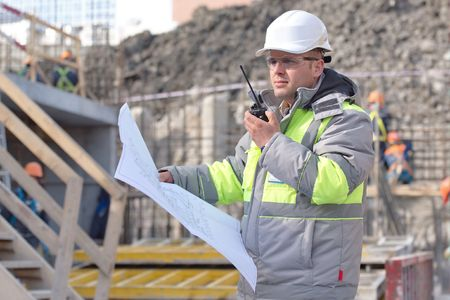Civil Engineer at at construction site is inspecting ongoing production according to design drawings. Stock Photo