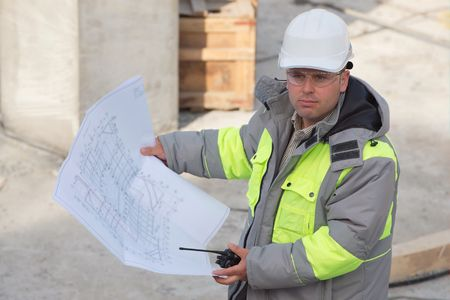 ongoing: Civil Engineer at at construction site is inspecting ongoing production according to design drawings. Stock Photo
