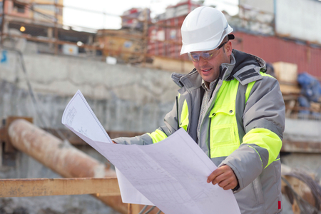 civil construction: Civil Engineer at at construction site is inspecting ongoing production according to design drawings. Stock Photo