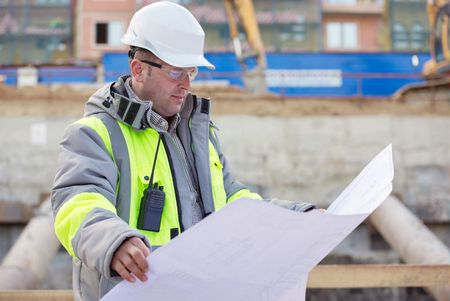 white collar worker: Civil Engineer at at construction site is inspecting ongoing production according to design drawings. Stock Photo